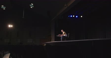 secundaria : Side view of a Caucasian high school teenage boy in an empty school theater preparing before a performance, sitting on a chair on the stage, holding a script and rehearsing his part