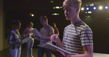 rehearsing : Side view of a Caucasian high school teenage boy in an empty school theatre during rehearsals for a performance, standing on the stage a holding script and practicing his lines, with others pupils holding scripts in the background, in slow motion Stock Footage