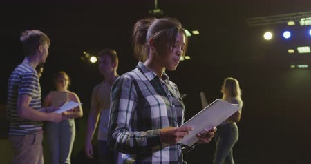 rehearsing : Side view of a African American high school teenage girl in an empty school theatre during rehearsals for a performance, standing on the stage holding a script and practicing her lines, with other pupilsholding scripts in the background, in slow motion Stock Footage