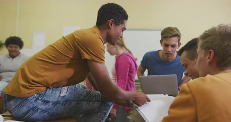 nuda : Side view of a multi-ethnic group of high school teenage male and female school pupils in a classroom studying, interacting and working together, using books and a tablet computer, in slow motion