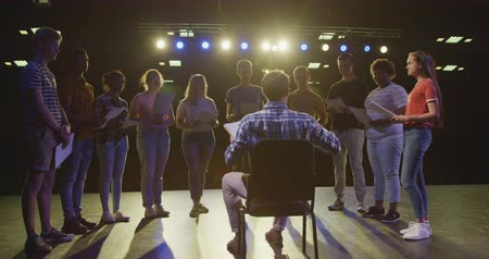 acteur : Rear view of a Caucasian male high school teacher sitting on a chair on the stage in an empty school theatre during rehearsals for a performance, holding a script, preparing a multi-ethnic group of teenagers for a performance, in slow motion
