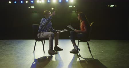 acteur : Side view of a Caucasian high school teenage girl and a Caucasian male teacher sitting on chairs on the stage in an empty school theatre preparing before a performance, holding scripts and practicing together, in slow motion