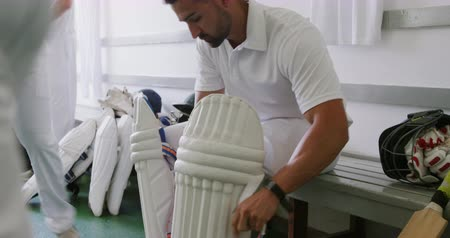 cricket pads : Side view of a mixed race male cricket player wearing whites, sitting on a bench in a changing room, putting on his cricket pads, with other players sitting and standing in the background