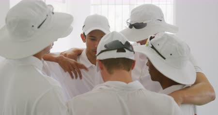 batedor : Side view of a group of teenage multi-ethnic male cricket players wearing whites, in a huddle in the changing room, preparing for a match