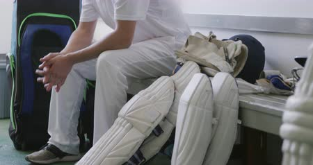 cricket pads : Side view of a teenage Caucasian cricket player wearing whites, sitting on a bench in a changing room, waiting before a cricket match, with cricket pads and helmets lying on the bench next to him.