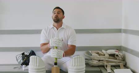 cricket pads : Front view of a mixed-race male cricket player wearing whites, sitting on a bench in the changing room, holding a cricket bat, focusing before a game