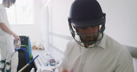 batedor : Side view of a mixed race male cricket player wearing whites, sitting on a bench in a changing room, putting on his cricket helmet, with another player preparing in the background