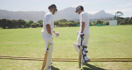 cricket pads : Side view of two teenage multi-ethnic male cricket players wearing whites and cricket helmets, standing on the pitch, fist-bumping and walking away from the camera in slow motion.