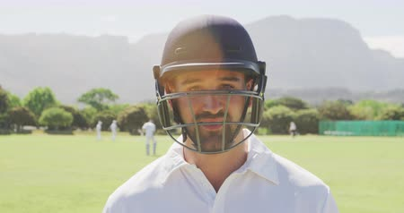 amontoado : Portrait of a confident mixed race male cricket player wearing white shirt and a cricket helmet, standing on a cricket pitch on a sunny day looking to camera, with cricket players standing in the background in slow motion.