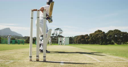 batedor : Low angle rear view of a teenage Caucasian male cricket player wearing a helmet and holding a cricket bat, swinging and failing to hit a ball thrown by a bowler in the background, in slow motion.