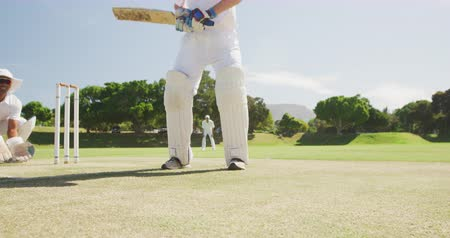 keeper : Low angle front view low section of a teenage Caucasian male cricket batsman wearing cricket pads and holding a cricket bat, hitting the ball on the pitch, with an Asian male wicket keeper in the background squatting behind, trying to catch the ball and f