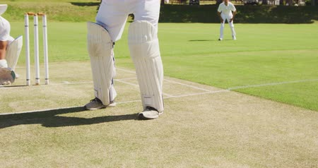 cricket pads : Front view low section of a teenage Caucasian male cricket batsman wearing cricket pads and holding a cricket bat, hitting the ball on the pitch, with an Asian male wicket keeper in the background squatting behind, trying to catch the ball and fielders in