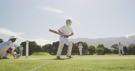 beyazlar : Side view of a teenage Caucasian male cricket player wearing a helmet and holding a cricket bat, trying to hit the ball on the pitch, with an Asian player in the background squatting, trying to catch the ball during a cricket match in slow motion Stok Video