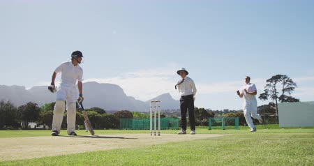 wicket : Front view of a teenage Caucasian male cricket player wearing whites, bowling the ball on the pitch during a cricket match, with an umpire standing in the background and a batsman running. Stock Footage