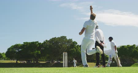 wicket : Side view of a teenage Caucasian male cricket player wearing whites, bowling the ball on the pitch during a cricket match, with an umpire standing in the background and a batsman hitting the ball, in slow motion