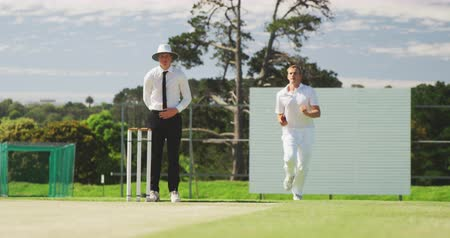 wicket : Front view of a teenage Caucasian male cricket player wearing whites, bowling the ball on the pitch during a cricket match, with an umpire standing in the background, slow motion Stock Footage