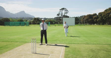 wicket : Front view of a teenage Caucasian male cricket player wearing whites, bowling the ball on the pitch during a cricket match, with the umpire standing in the background watching, slow motion