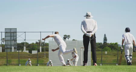 wicket : Rear view of a teenage Caucasian male cricket player wearing whites, bowling the ball, then celebrating on the pitch during a cricket match, with other players in the background and the umpire watching, in slow motion