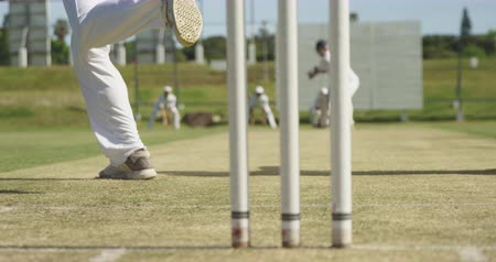 wicket : Rear view low section of a teenage Caucasian male cricket player wearing whites, bowling the ball on the pitch during a cricket match, with a batsman trying to hit the ball in the background, in slow motion