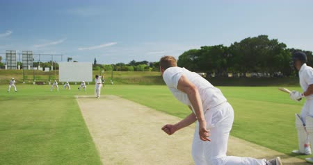 wicket : Rear view of a teenage Caucasian male cricket player wearing whites, throwing the ball on the pitch during a cricket match, with another player trying to hit the ball in the background, in slow motion