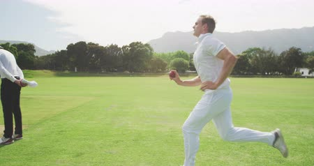 wicket : Side view of a teenage Caucasian male cricket player wearing whites, running and bowling the ball on the pitch during a cricket match, with an umpire and batsman standing in the background, in slow motion Stock Footage