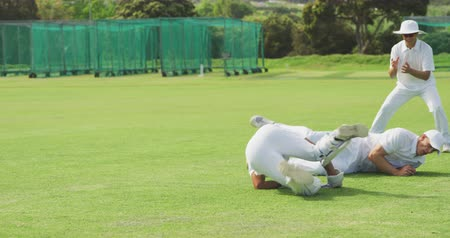 wicket : Front view of a teenage multi-ethnic male cricket team wearing whites, standing on a cricket pitch, diving for the ball during a match on a sunny day in slow motion Stock Footage