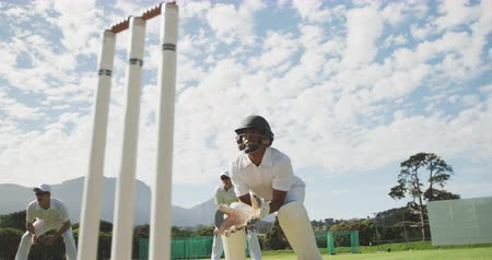 cricket pads : Low angle front view of a teenage African American male cricket player wearing whites, helmet and gloves, standing on the pitch playing the wicket keeper position during a cricket match, squatting, jumping and catching the cricket ball, in slow motion