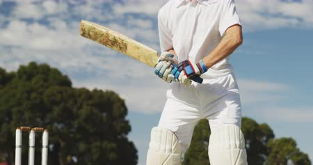 cricket pads : Side view close up of a teenage Caucasian male cricket player on the pitch wearing helmet and gloves, holding a cricket bat, swinging and hitting the ball during a cricket match, against blue cloudy sky, in slow motion