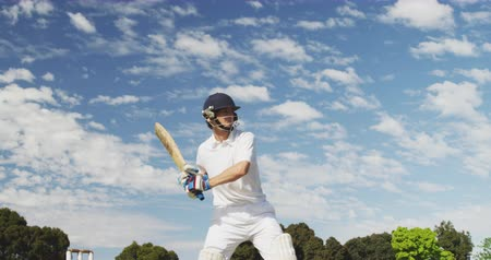 cricket pads : Side view of a teenage Caucasian male cricket player on the pitch wearing helmet and gloves, holding a cricket bat, swinging and hitting the ball during a cricket match, against blue cloudy sky, in slow motion