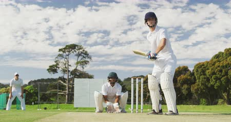 cricket pads : Front view of a teenage Caucasian male cricket player on the pitch wearing helmet and gloves, holding a cricket bat, hitting the ball and making a run during a cricket match, with a wicket keeper and another player in the background, in slow motion