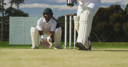 cricket pads : Front view low angle of a teenage Caucasian male cricket player on the pitch wearing helmet and gloves, holding a cricket bat and hitting the ball during a cricket match with the wicket keeper squatting behind him in the background, in slow motion Stock Footage