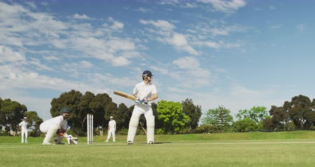 cricket pads : Side view of a teenage Caucasian male cricket player on the pitch wearing helmet and gloves, holding a cricket bat, and hitting the ball during a cricket match with other players on the pitch in the background, in slow motion