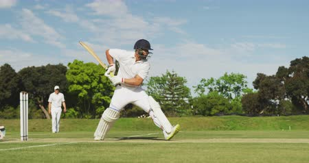 wicket : Side view of a teenage Caucasian male cricket player on the pitch wearing helmet and gloves, holding a cricket bat, hitting the ball and making a run during a cricket match, with other players on the pitch in the background, in slow motion
