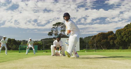cricket pads : Front view of a teenage Caucasian male cricket player on the pitch wearing helmet and gloves, holding a cricket bat and hitting the ball during a cricket match with other players in the background, in slow motion