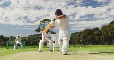 cricket pads : Front view of a teenage Caucasian male cricket player on the pitch wearing helmet and gloves, holding a cricket bat, failing to hit the ball and getting bowled out during a cricket match, with a wicket keeper and other players in the background in slow mo