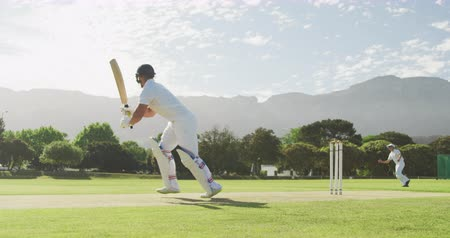 cricket pads : Side view of a teenage Caucasian male cricket player on the pitch wearing helmet and gloves, holding a cricket bat, hitting the ball and making a run during a cricket match, with other players on the pitch in the background, in slow motion