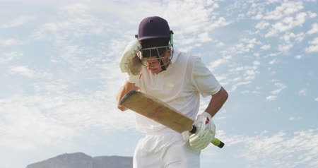 cricket pads : Low angle front view of a teenage Caucasian male cricket player wearing whites, standing on the pitch, smiling and raising his hands, holding a cricket bat and a cricket helmet, shouting, celebrating in slow motion