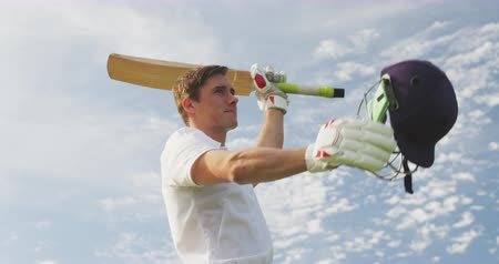 cricket pads : Low angle front view of a teenage Caucasian male cricket player wearing whites, standing on the pitch, smiling and raising his hands, holding a cricket bat and a cricket helmet, celebrating, in slow motion