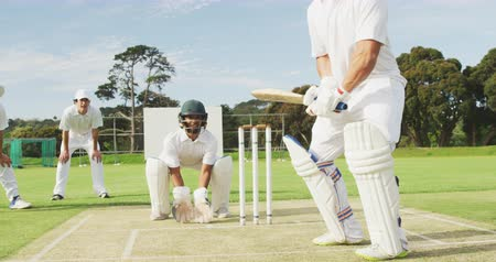 cricket pads : Front view of a teenage Caucasian male cricket player on the pitch wearing helmet and gloves, holding a cricket bat and hitting the ball during a cricket match, with the wicket keeper and other players in the background, in slow motion