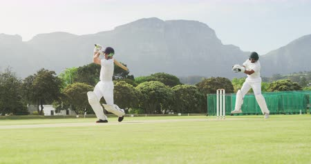 cricket pads : Side view of a teenage Caucasian male cricket player on the pitch wearing helmet and gloves, holding a cricket bat, failing to hit the ball and being stumped by teh wicket keeper during a cricket match, with players celebrating in the background, in slow