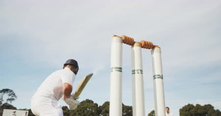 cricket pads : Rear view low angle of a teenage Caucasian male cricket player on the pitch wearing helmet and gloves, holding a cricket bat, failing to hit the ball during a cricket match and being stumped, the hand of the wicket keeper in the foreground, in slow motion