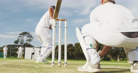 cricket pads : Rear view of a teenage Caucasian male wicket keeper and batsman on the pitch wearing helmet and gloves, the batsman failing to hit the ball and being bowled out, during a cricket match in slow motion