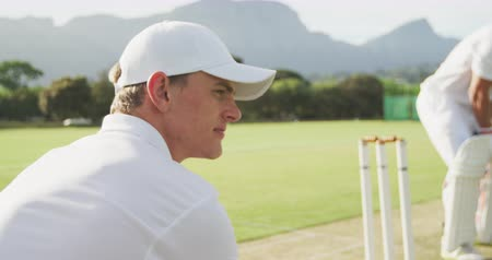 cricket pads : Side view of a teenage Caucasian male cricket player on the pitch wearing whites and a cap, squatting in the wicket keeper position, turning his head to the camera and smiling during a cricket match, in slow motion Stock Footage