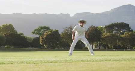 beyazlar : Front view of a Caucasian male cricket player wearing whites and a hat, standing on a cricket pitch and catching the ball during a match on a sunny day, in slow motion
