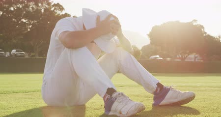 perdedor : Side view close up of a sad teenage mixed race male cricket player wearing whites and a hat, sitting on the pitch, holding and shaking his head after the match on a sunny day, slow motion