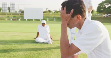perdedor : Side view of a disappointed teenage mixed race male cricket player wearing whites, sitting on the pitch, holding his head after the match on a sunny day, with other players in the background, slow motion