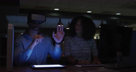 designing : Front view of a Caucasian businessman and a mixed race businesswoman working late in a modern office, the man wearing Visual Reality headset and touching with his hand virtual interactive screen, the woman typing on computer keyboard