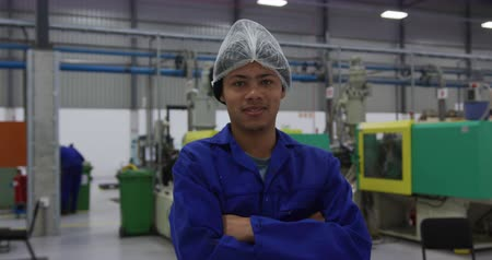 crate : Portrait of focused mixed race male worker wearing overalls and a hair net standing with arms crossed, looking to camera and smiling, in a busy factory warehouse