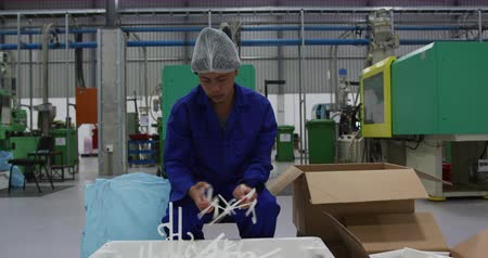 repartidor : Front view of focused mixed race male worker working in a busy factory warehouse, wearing hair net preparing and packing plastic parts