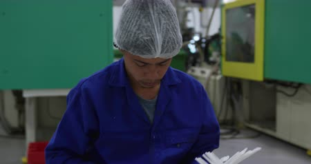 engradado : Front view close up of focused mixed race male worker working in a busy factory warehouse, wearing a hair net and overalls, preparing and packing plastic parts Stock Footage